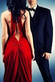 stock photo of red back  - Beautiful young couple in love in evening dresses posing at studio - JPG