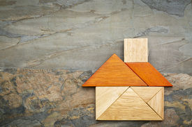 stock photo of tangram  - abstract picture of a house built from seven tangram wooden pieces against slate rock background - JPG