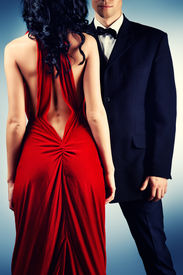 stock photo of slender  - Beautiful young couple in love in evening dresses posing at studio - JPG