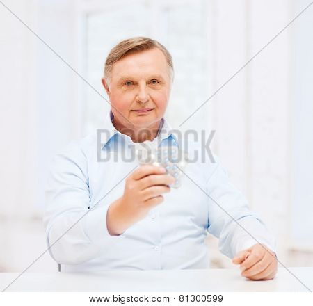 healthcare, medicine, pharmacy and elderly concept - old man with pack of pills