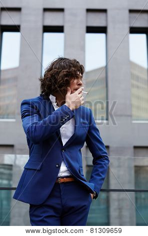 Portrait of a smart business executive smoking cigar looking concerned