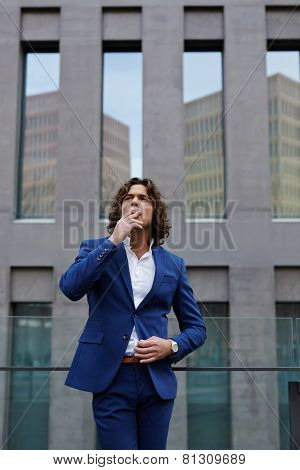 Portrait of wealthy confident gentleman smoking a cigarette standing near office building