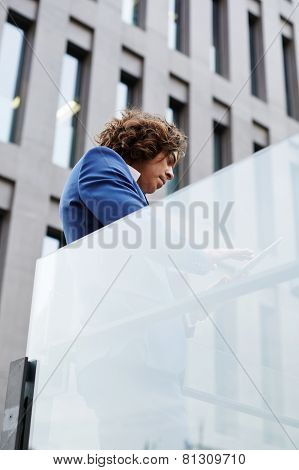 Shot of a mature businessman standing against office building using a digital tablet