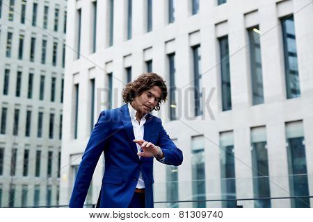 Young businessman walking in the street and looking down at his watch