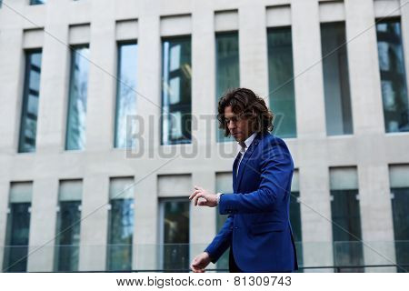 Portrait of a young business man checking time while walking on city street