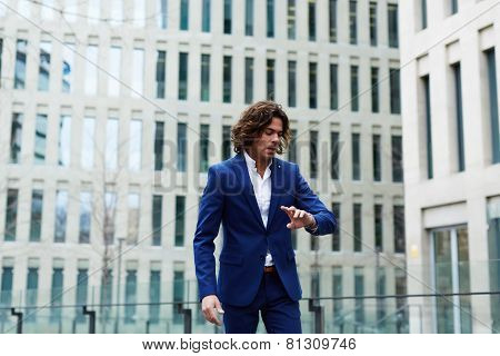 Portrait of young business man checking time and walking in the city
