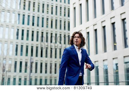 Portrait of young business man checking the time and walking in city