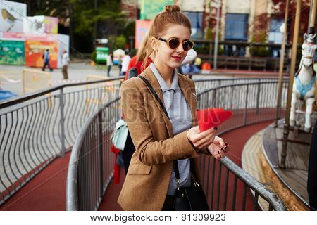 Stylish woman in glasses holding tickets for ride on carousel in amusement park