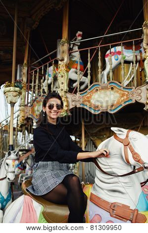 Attractive young woman having fun riding on carousel in amusement park