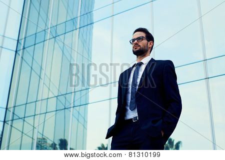 Confident business man in glasses standing against office building with hands in the pockets