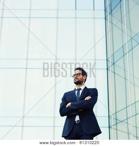 Upper half portrait of handsome business man in glasses standing near skyscraper office building