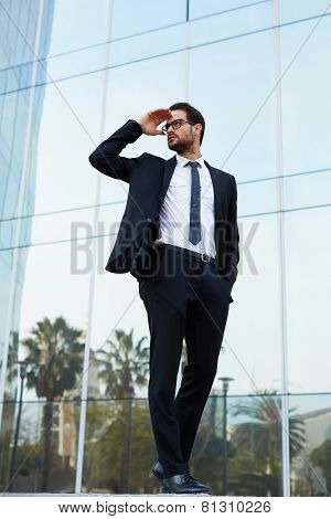 Full length portrait of young businessman looking off in the distance holding up his hand