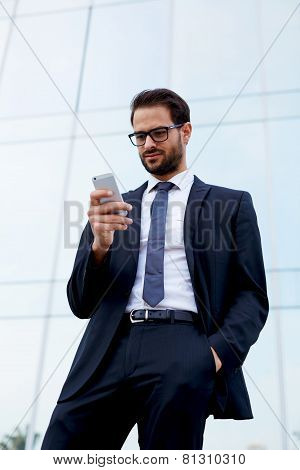 Half length of businessman reading text message on cellphone with on hand in pocket