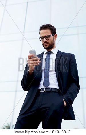 Young successful executive using mobile phone standing near office building at beautiful day