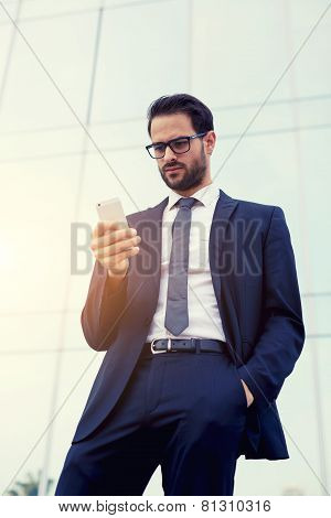 Half length portrait of handsome businessman reading text message on his smartphone