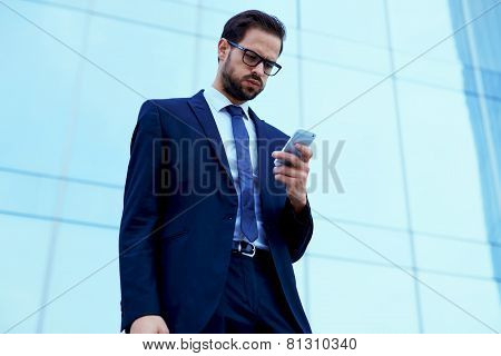 Unhappy employee read text message on cell phone standing against skyscraper office building
