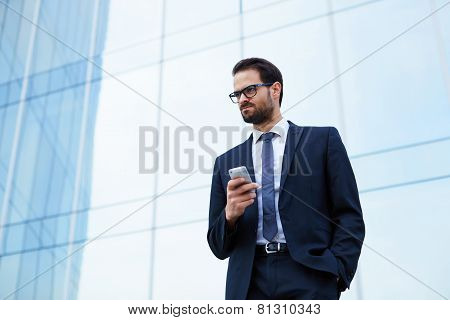 Portrait of angry business man holding his mobile phone while standing at office building