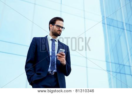Portrait of young executive looking stressed standing near office with smart-phone in the hand