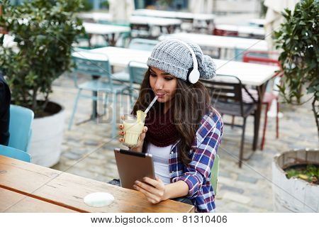 Stylish hipster girl drinking fruit cocktail and use digital tablet in coffee shop