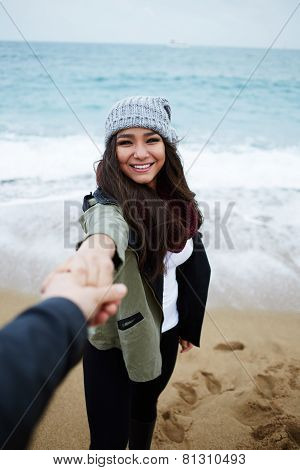 Portrait of charming girlfriend holding boyfriend hand young couple in love at romantic walk.