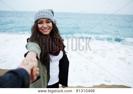 Portrait of laughing woman in love with hand held by her boyfriend standing against the ocean