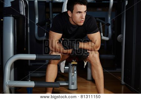 Handsome young man resting after fitness training while sit on machine equipment