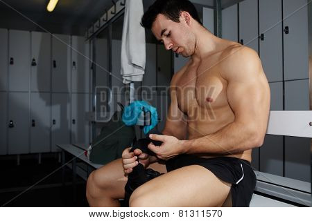 Professional athlete removing weight lifting gloves sitting in gym's locker room after workout
