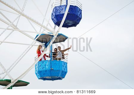 Company of young attractive men traded on the Ferris wheel in good sunny day