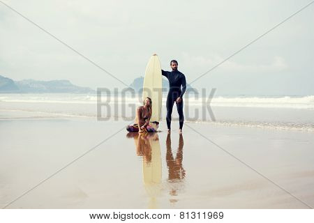 Beautiful surfer couple standing on the beach before their sunday surf lesson