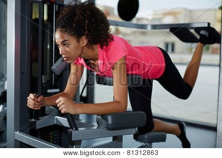 Side view of young athletic girl working out at gym doing exercise for buttocks and legs