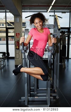 Attractive dark skinned girl working out for abs muscles at gym
