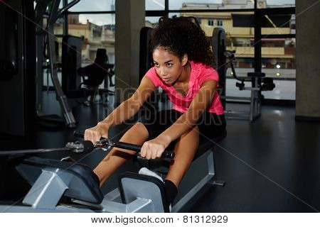 Attractive afro american woman with curly hair working out at gym doing legs exercise on press machi