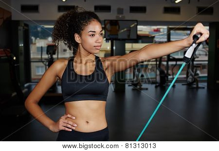 Portrait of beautiful fitness woman working out with resistance expander in gym