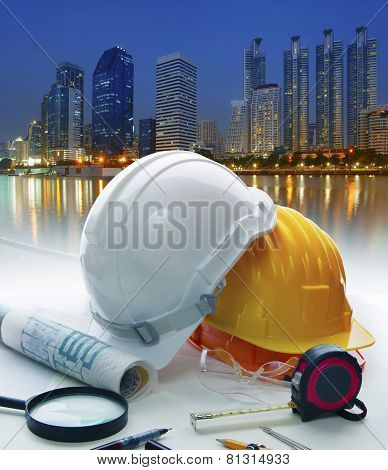Engineer Working Table With Safety Helmet And Writing Equipment Against Beautiful Lighting Of Buildi