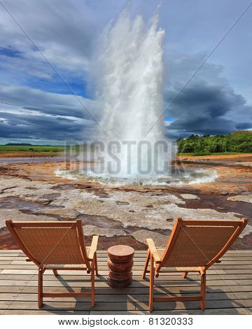 Geyser Strokkur in Iceland. Pillar of hot water and steam from forcing its way out of the ground. Two lounge chairs and  small table on  wooden platform for easy observation