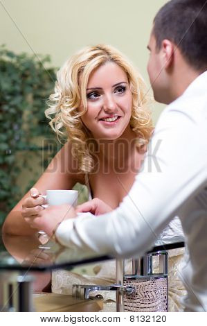 Young happy couple drinking coffee in a restaurant