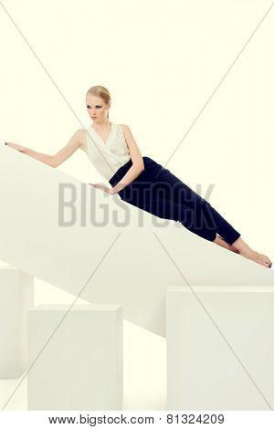 Fashionable female model posing at studio. Beauty, fashion photo. Clothing. Body care. Isolated over white.