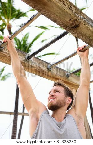 Workout fit man working out arm training on brachiation horizontal ladder or monkey bars in outside beach gym outdoors.
