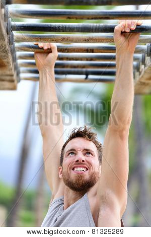 Fit man cross training on monkey bars station. Fitness workout on brachiation ladder in an outdoor gym outside. Male athlete swinging on high bars exercising.