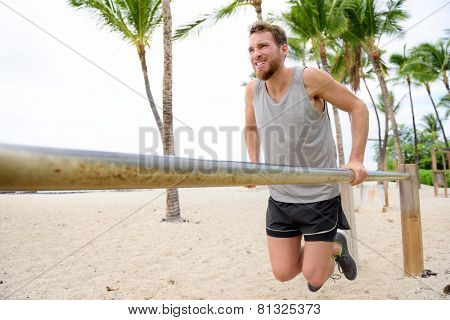 Bodyweight exercises man workout on dips bars. Male adult working out triceps and biceps on horizontal bars on beach as crossfit training routine.