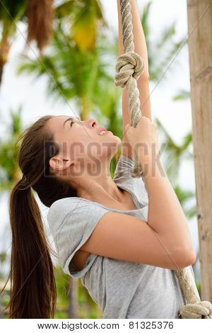 Exercise fit woman doing body workout on climbing rope as toning exercises for arm toning. Cro