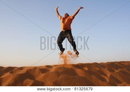 Man jumping for joy in Dubai desert