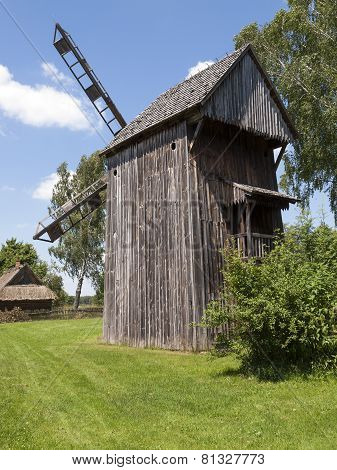 Old wooden windmill on background of blue sky