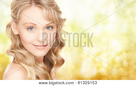 people, beauty, body and skin care concept - beautiful woman face and hands over yellow lights background