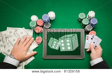 casino, online gambling, technology and people concept - close up of poker player with playing cards, tablet pc computer and chips at green casino table