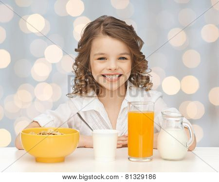healthy food, eating, people and children concept - happy smiling beautiful girl having breakfast over holidays lights background