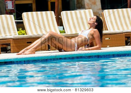 Relaxed Woman Tanning At Resort Swimming Pool