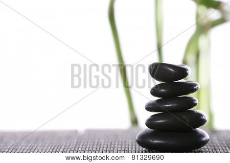 Stack of spa stones on bamboo mat surface with bamboo sticks isolated on white
