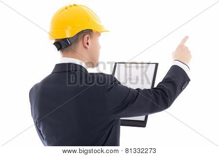 Young Handsome Business Man In Yellow Builder's Helmet With Blueprint Pointing On Something Isolated