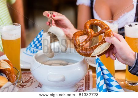 People eating veal sausage in bavarian restaurant